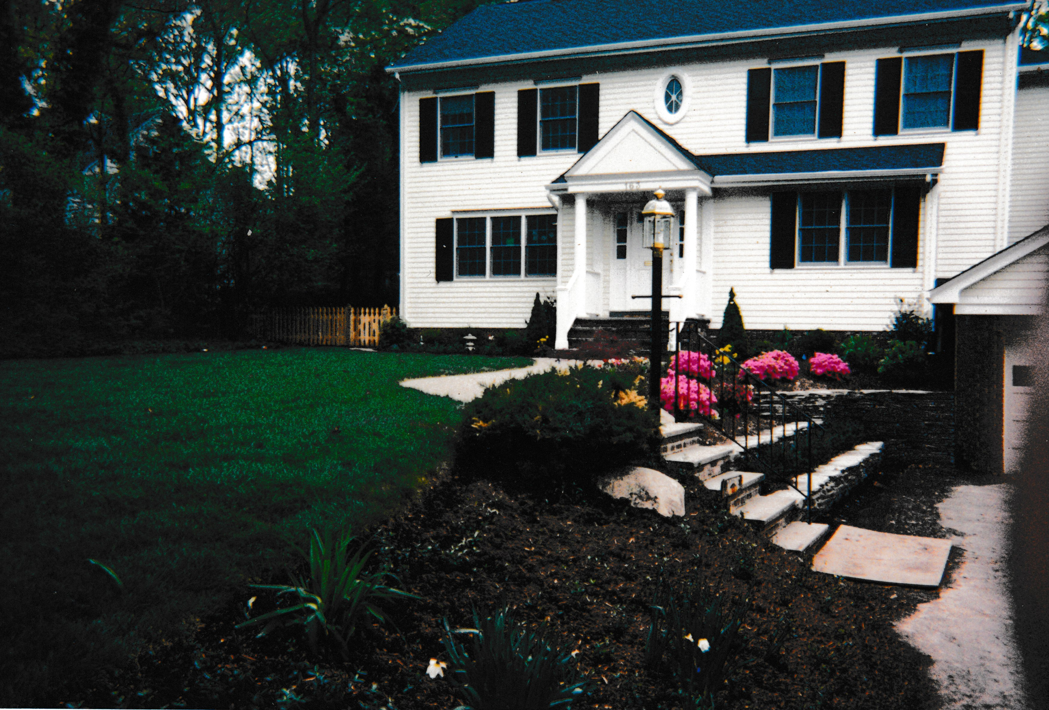 Front yard with colorful shrubbery and brick stairway