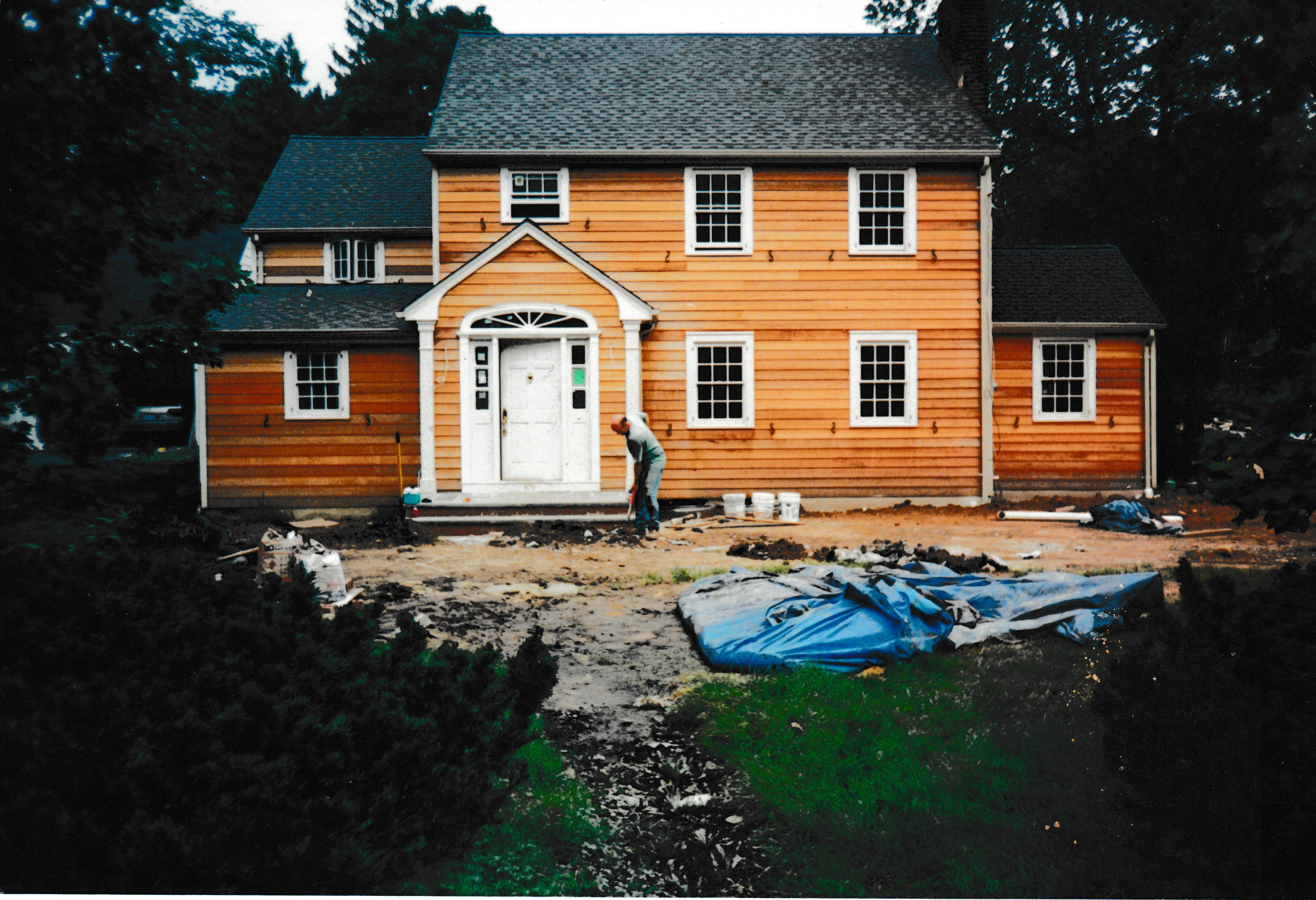 House under construction, worker digging up ground