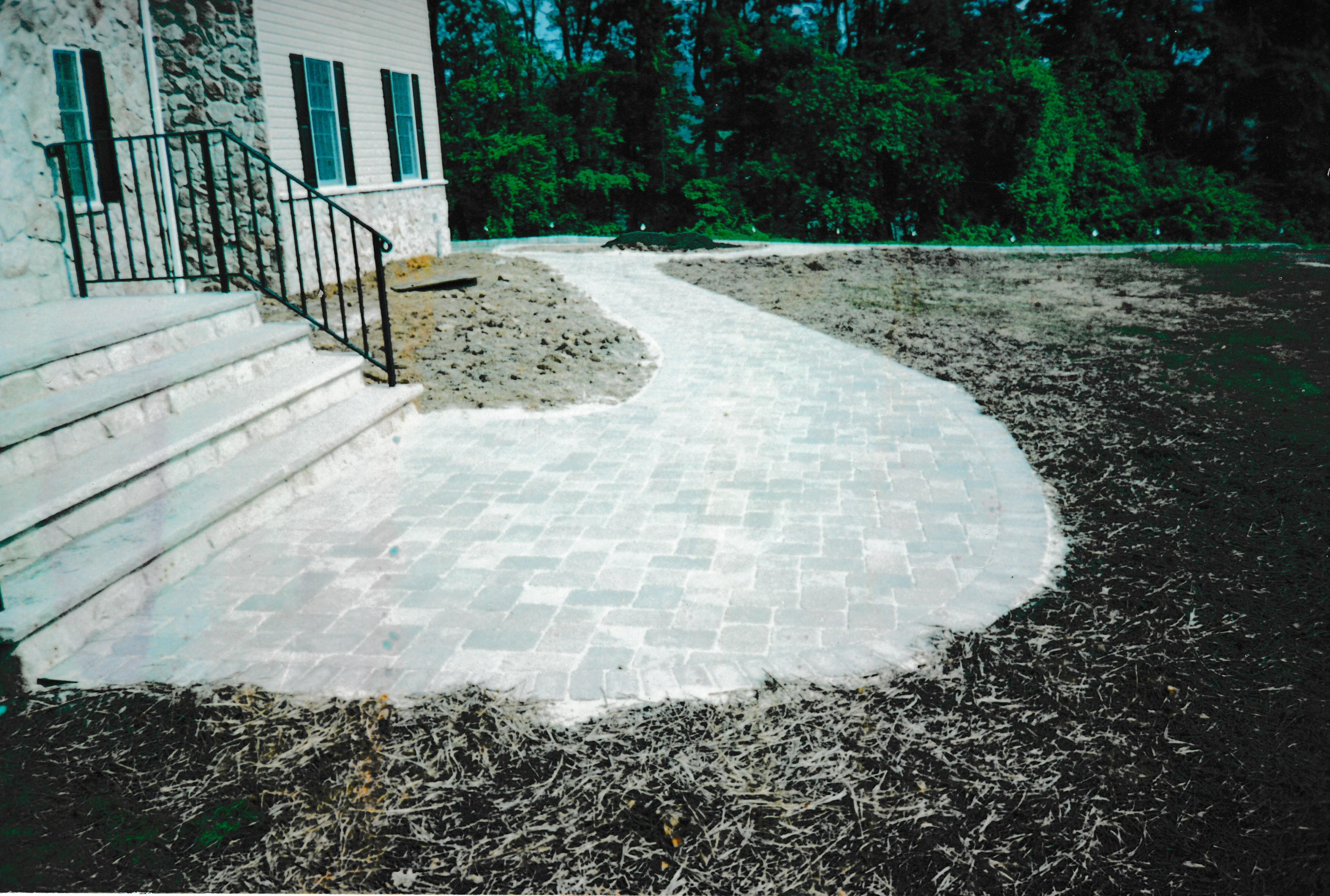 Finished brick walkway leading to front stairs of house